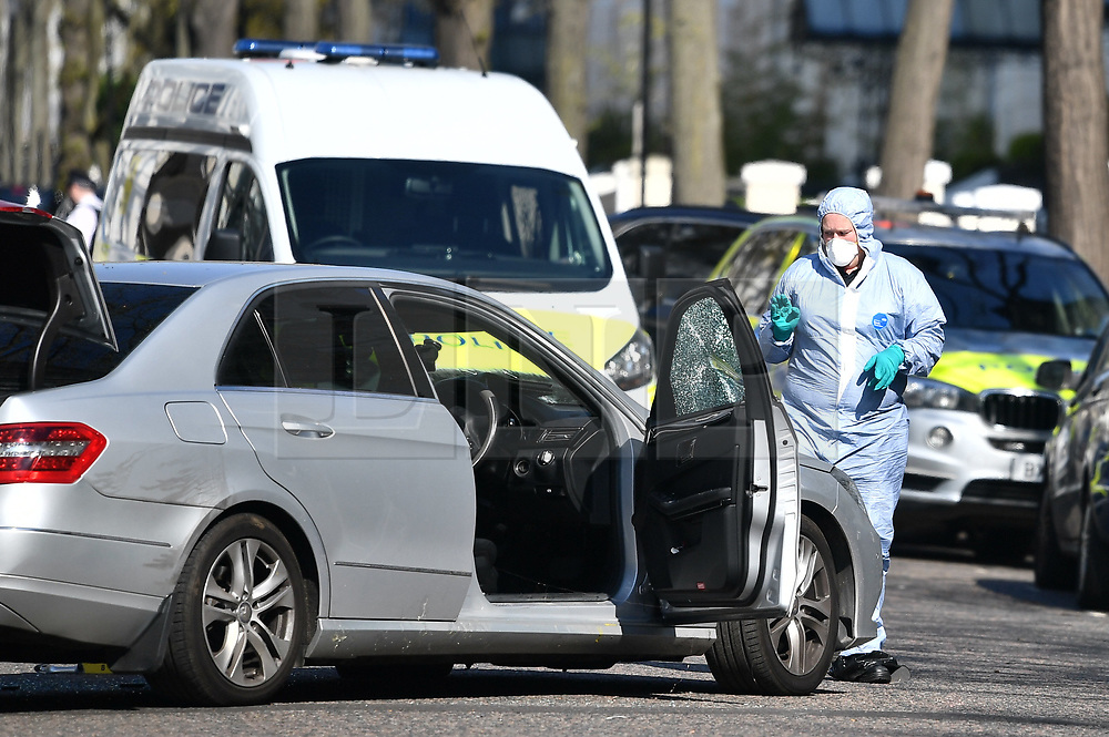 © Licensed to London News Pictures. 13/04/2019. London, UK.  Forensics examine a damaged car at The scene in Holland Park after shots were fired near the Ukranian embassy. Photo credit: Ben Cawthra/LNP