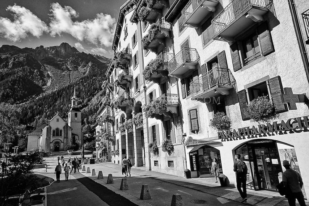 Black and white street view of Hotel De Ville, shops, a church, and the French Alps - Chamonix, France (Horizontal).