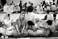 "AOF.LI.041904.SDL -- From left, Jasmine Grewal, 16, Jaspreet Cheema, 13, Nanki Chatrath, 12, and Manreet Singh, 13, laugh at each other during the community meal after the end of Baisakhi Day celebrations at the Sikh Gurudwara in Durham. Baisakhi Day, which falls on April 13th or 14th depending on the year, celebrates the birth of Sikhism in 1699 in Punjab, a state in the northern region of modern day India. The community meal is open to the community and all diners, regardless of status, sit on the floor. When this was originially done 305 years ago, it was a revolutionary idea since it was contrary to the caste system that placed certain people on a higher spiritual and social level than others. ""We are all low in front of God,"" Dharampal Singh, a member of the Gurudwara, said of the tradition's message."