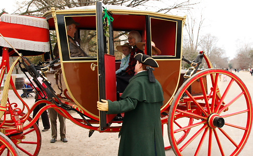 elegant carriage; red wheels & frame; driver in long cape talking to family inside; Colonial Williamsburg; Williamsburg; VA; Virginia, winter