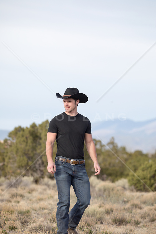 cowboy outdoors by a mountain range