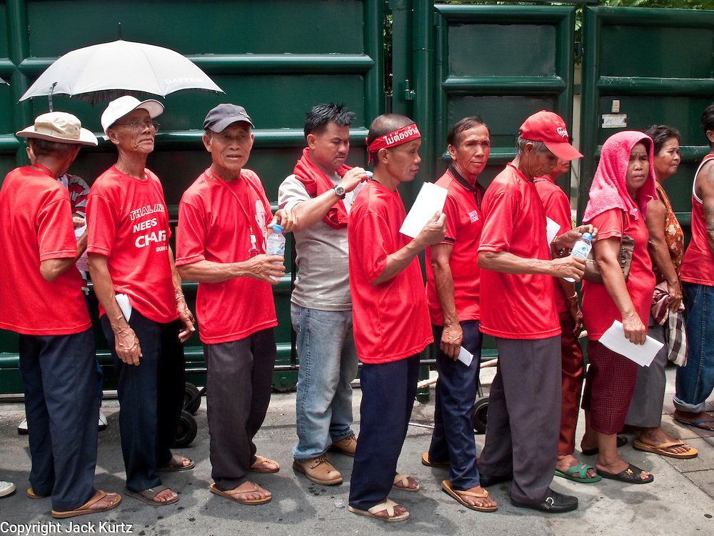 04 MAY 2010 - BANGKOK, THAILAND:   Red Shirt demonstrators wait in line to get their ID cards in Bangkok Tuesday. Red Shirt protesters continued their actions in Bangkok Tuesday despite heavy thunderstorms that brought rain to the city. The Red Shirts have conditionally accepted the offer of Thai Prime Minister Abhisit Vejjajiva to dissolve parliament, investigate alleged human rights violations following the violence of April 10 and call for new elections in November of this year, 18 months earlier than they are currently scheduled, but they want more negotiation before they finalize any agreements. They said their protests would continue until a final agreement is reached. The Red Shirts, started their protest on March 13. They continue to call for Thai Prime Minister Abhisit Vejjajiva to step down and dissolve parliament immediately and demand the return of ousted Prime Minister Thaksin Shinawatra.     PHOTO BY JACK KURTZ