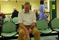 Patient with guide dog in waiting room of eye clinic at QMC hospital, Nottingham.