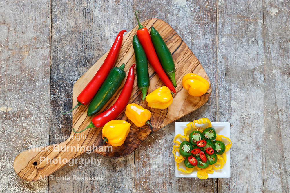 Overhead view of red, green and yellow hot peppers on wooden board with sliced peppers in white bowl on old wooden table