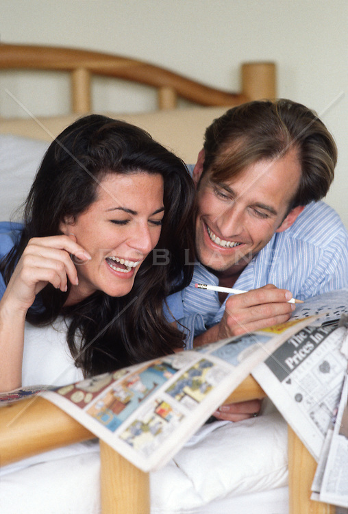 Couple in bed doing a cross word puzzle