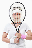 Portrait of an Asian young woman looking through tennis racket over white background