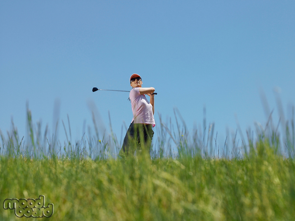 Young female golfer driving ball low angle view