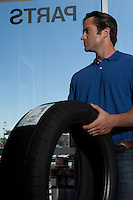 Side view of man holding tire