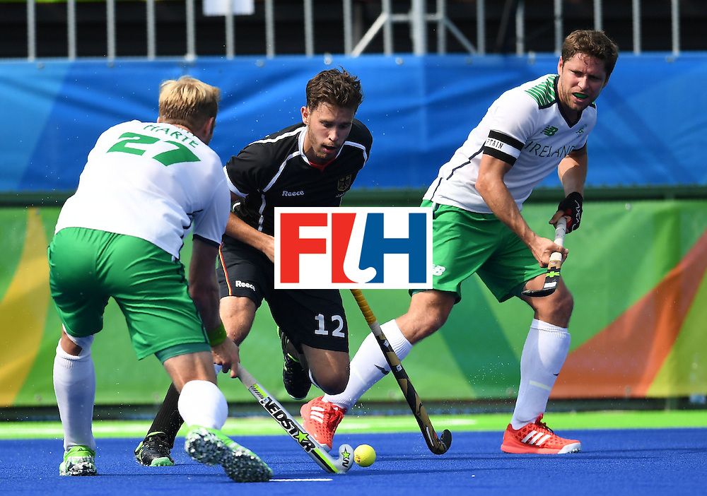 Germany's Timm Herzbruch(C) tries to block Ireland's Conor Harte during the men's field hockey Germany vs Ireland match of the Rio 2016 Olympics Games at the Olympic Hockey Centre in Rio de Janeiro on August, 9 2016. / AFP / MANAN VATSYAYANA        (Photo credit should read MANAN VATSYAYANA/AFP/Getty Images)