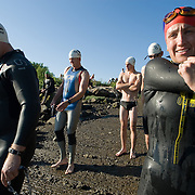 A female triathlete wearing a red swim cap stretches as she and other athletes near the banks of the Kennebec river.  2007 Shipbuilders Triathlon in Bath, Maine.