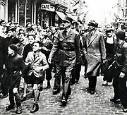 Charles de Gaulle (1890-1970) French General and first President of The Fifth Republic. De Gaulle walking through Bayeux, the first French town to be liberated, surrounded by rejoicing populace.  On his left is Vienot, representative of the French provisional government in London.  World War II: 14 June1944.