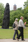 © Licensed to London News Pictures. 07/06/2012. Kew, UK Visitors walk past 'Charred Cross Egg' created in 2008 from Charred Oak' The Royal Botanic Gardens, Kew, hosts a photocall for an exhibition of sculpture by David Nash in the grounds and Temperate Houses. The exhibition opens to the public on 9th June 2012 and finishes on 14th April 2013  Photo credit : Stephen Simpson/LNP