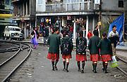 Schoolgirls in uniform walk between the tracks of the narrow gauge mountain railway in Ghum, near Darjeeling, West Bengal, India