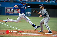 Aug 23, 2014; Toronto, Ontario, CAN; Toronto Blue Jays centre field  Colby Rasmus (28) stretches to make first base with Tampa Bay Rays first base Sean Rodriguez (1) watching after bunting ball in tenth innings at Rogers Centre - Blue Jays won 5-4 in tenth innings. Mandatory Credit: Peter Llewellyn-USA TODAY Sports