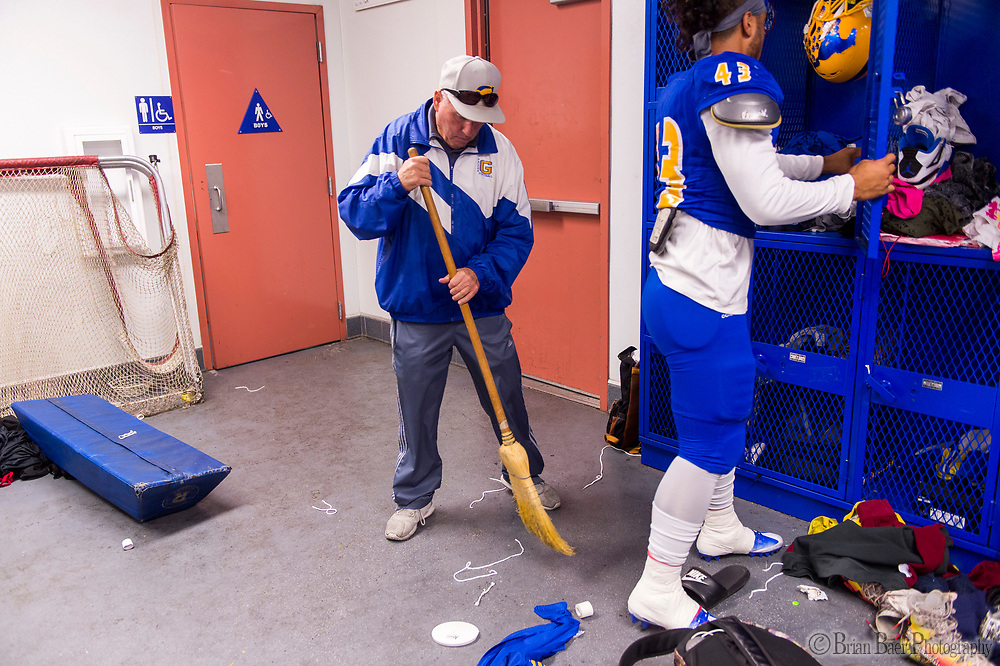 Grant Pacers head coach Mike Alberghini, sweeps up trash in the locker room before the game as the Grant High School Pacers varsity football team host the Sheldon High School Huskies football team, Friday Oct 20, 2017.<br /> photo by Brian Baer