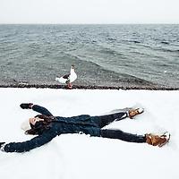 """Eine zutrauliche Gans (Pommerngans/Graugans/Anser anser), schaut einer jungen Frau  beim """"Engelchen im Schnee machen"""" zu. Starnberger See, Berg, Bayern, Deutschland."""