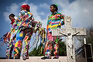 Un grupo de Diablos permanece sobre la tumba de un familiar durante la festividad del Corpus Christi, representada en Venezuela a traves del ritual magico-religioso de los Diablos Danzantes. Los Diablos de Naiguata se identifican por pintar sus propios trajes y decorarlos con cruces, rayas y circulos, figuras que impiden que el maligno los domine. Las mascaras son en su gran mayoria animales marinos. Llevan escapularios cruzados, crucifijos y cruces de palma bendita. Naiguata, 30 Mayo 2013. (ivan gonzalez)