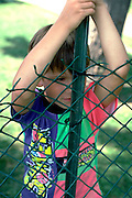 6 year old looking through a fence at Aquatennial event.  Minneapolis  Minnesota USA