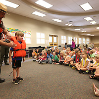 Adam Robison | BUT AT PHOTOS.DJOURNAL.COM<br /> Stihl Beane, a kindergartener at Saltillo Primary School, helps Park Ranger Chris Gurner, demonstrate the proper use of fitting into and wearing a life preserver vest during water safety day at Saltillo Primary School Wednesday morning in Saltillo.
