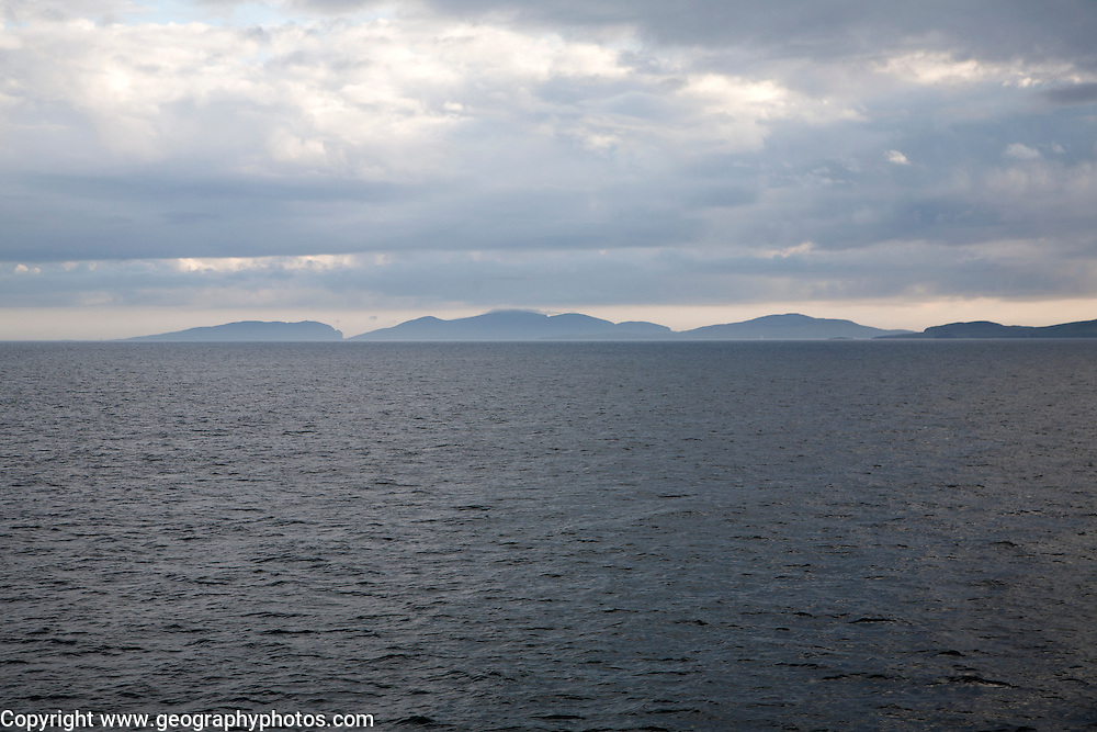 Distant view over sea to hills on Barra, Outer Hebrides, Scotland, UK