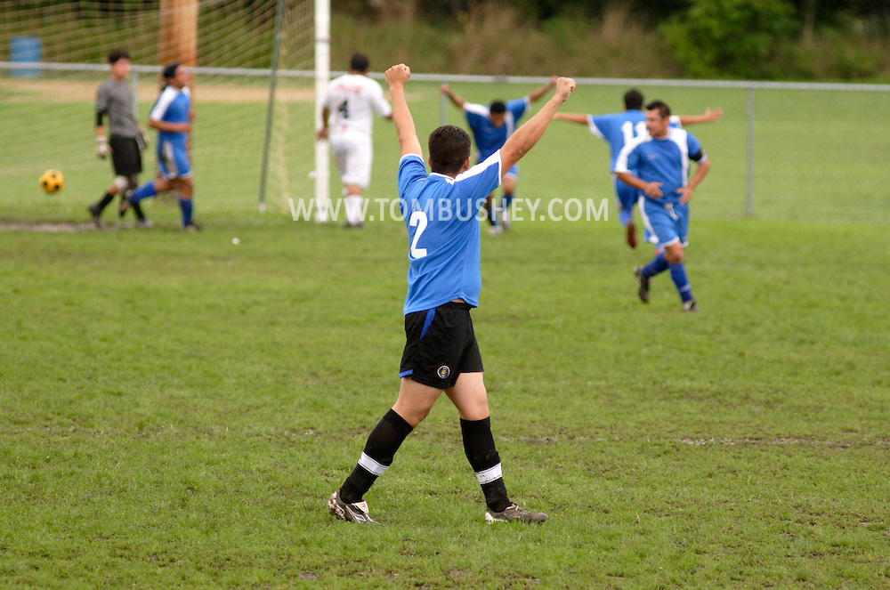 Middletown, N.Y. - A player raises his arms after his team scores a goal during a soccer game in a predominantly Latino men's soccer league on Sept. 3, 2006.