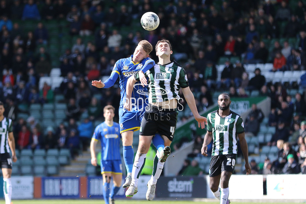 Jake Reeves midfielder for AFC Wimbledon (8) and Plymouth Argyle defender Carl McHugh (4) during the Sky Bet League 2 match between Plymouth Argyle and AFC Wimbledon at Home Park, Plymouth, England on 9 April 2016. Photo by Stuart Butcher.