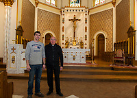 Facilities Director Cory Johnson and Father Marc Drouin stand at the alter of the newly renovated Sacred Heart Church in Laconia.  (Karen Bobotas/for the Laconia Daily Sun)