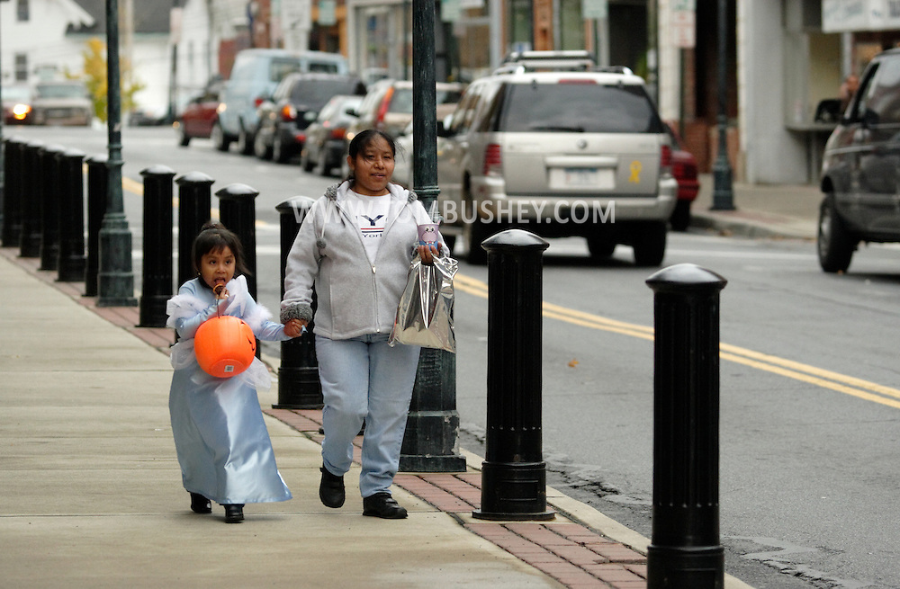 Middletown, N.Y. -  A girl in a costume and an adult walk down North Street to get candy in stores after a Halloween Parade on Oct. 28, 2006. ©Tom Bushey