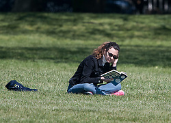 © Licensed to London News Pictures. 20/04/2020. London, UK. A woman sitting down and reading a book in Primrose Hill, north London during a pandemic outbreak of the Coronavirus COVID-19 disease. The public have been told they can only leave their homes when absolutely essential, in an attempt to fight the spread of coronavirus COVID-19 disease. Photo credit: Ben Cawthra/LNP. Photo credit: Ben Cawthra/LNP