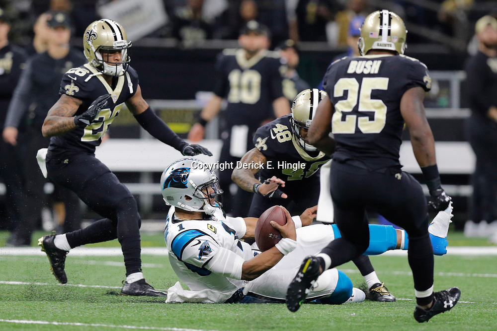 Jan 7, 2018; New Orleans, LA, USA; Carolina Panthers quarterback Cam Newton (1) slides after running against New Orleans Saints cornerback P.J. Williams (26) and free safety Vonn Bell (48) and defensive back Rafael Bush (25) during the first quarter in the NFC Wild Card playoff football game at Mercedes-Benz Superdome. Mandatory Credit: Derick E. Hingle-USA TODAY Sports
