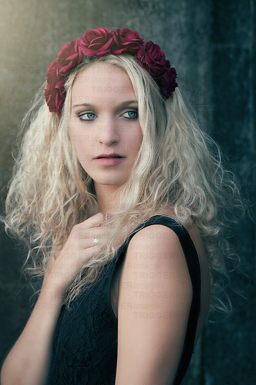 Portrait of a fairy young woman with blonde curly hair and roses in her hair