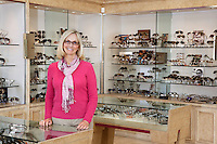 Portrait of a happy senior female optician standing in store