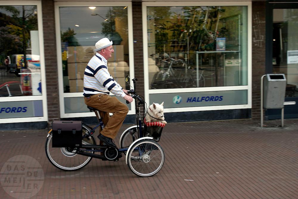 Een man fietst met een hond in een mandje op een aangepaste fiets door het centrum van Nijmegen.<br /> <br /> A man is cycling with a dog in a basket on a special bike in the center of Nijmegen.