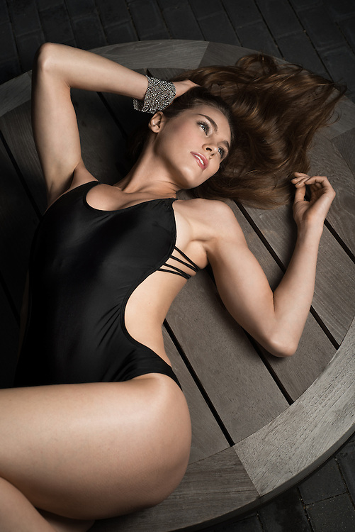 Beautiful young woman is lying on top of wooden table in black one-piece swimsuit.