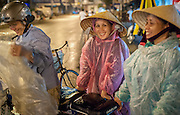 Three women in raincoats under the rain (Vietnam)