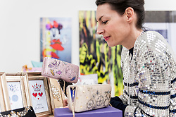 © Licensed to London News Pictures. 22/02/2016. London, UK.  Textile designer, Veronica Catani, of Vera Givel examines her display as Scoop London takes place at the Saatchi Gallery in Chelsea.  Running concurrently with London Fashion Week AW16, the show attracts fashion buyers from around the world who come to meet designers presenting their products amongst the gallery's artworks. Photo credit : Stephen Chung/LNP