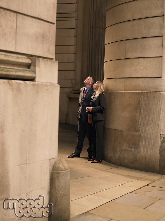 Businessman and businesswoman standing at entrance to monumental building looking up