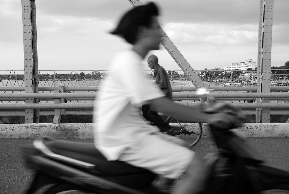 Two generations, a young man on a motorbike and an old man on a bicycle, pass each other on a bridge in Hue, Vietnam