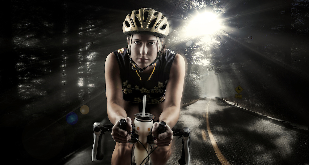 A composite image of female triathlete training on her bike riding on a paved road that wanders through a mystic dark forest while the suns morning rays pierce through the canopy.
