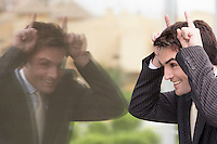 Businessman Making Faces in Window