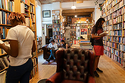 Customers browsing books inside St Georges secondhand bookshop in Prenzlauer berg, Berlin, Germany