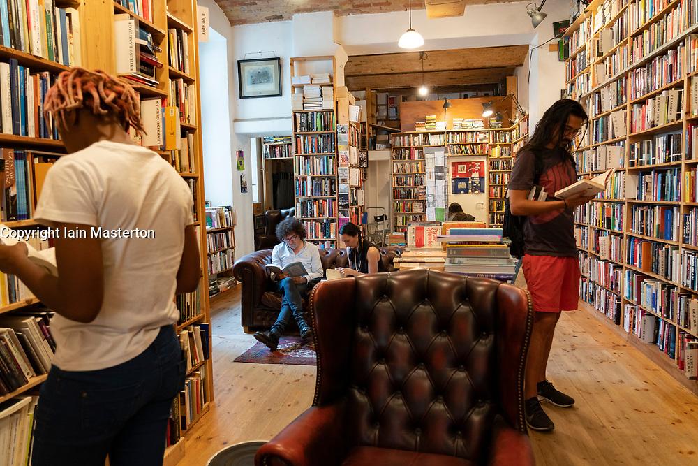 Customers browsing books inside St Georges secondhand bookshop in Prenzlauer berg, Berlin, Germany