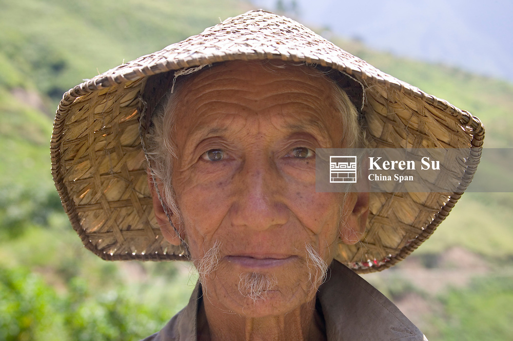 Portrait of an old farmer wearing bamboo hat, Trashing Yangtse Valley, east Bhutan