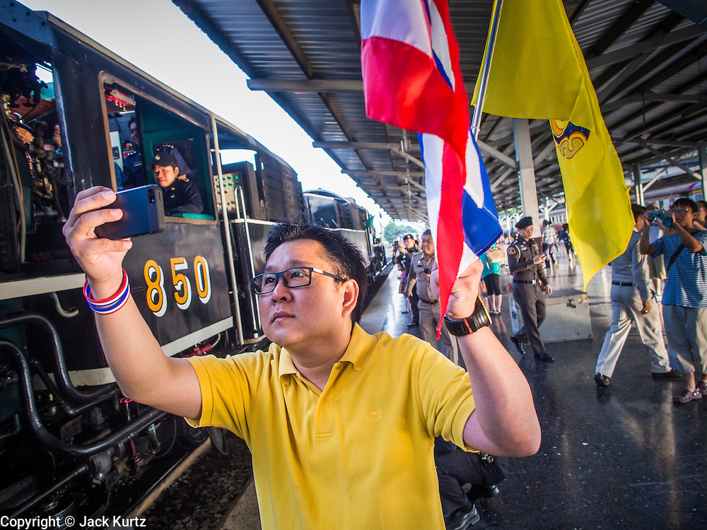 "05 DECEMBER 2013 - BANGKOK, THAILAND:  A man holding the Thai flag and the King's flag photographs a special steam engine train leaving Hua Lamphong Train Station on the 86th birthday of Bhumibol Adulyadej, the King of Thailand. Dec. 5, the King's Birthday, is a national holiday in Thailand, and is also celebrated as the country's ""Fathers' Day."" The State Railways of Thailand put on special trains to take people to the King's ""Summer Palace"" in the oceanside community of Hua Hin where the King granted a public audience. There were also merit making ceremonies throughout the country.  Many people wear yellow on the King's Birthday because yellow is the color associated with his reign. As of 2013, he was the longest reigning monarch in the world.          PHOTO BY JACK KURTZ"