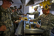 "Curtis Newcomer (left),  a soldier at the National Training Center at Fort Irwin, California, getting breakfast at the mess tent. (Curtis Newcomer is featured in the book What I Eat: Around the World in 80 Diets.) The caloric value of his day's worth of food in the month of September was 4,000 kcals. He is 20; 6'5"" and 195 pounds."
