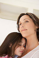 Mother cuddling daughter head and shoulders