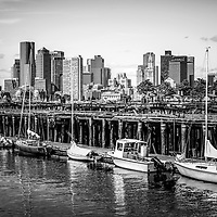 Boston skyline at Piers Park black and white photo. Picture includes downtown Boston skyscraper buildings, old Boston Harbor piers, and boats.