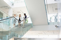 Businesswomen conversing while moving down steps in office