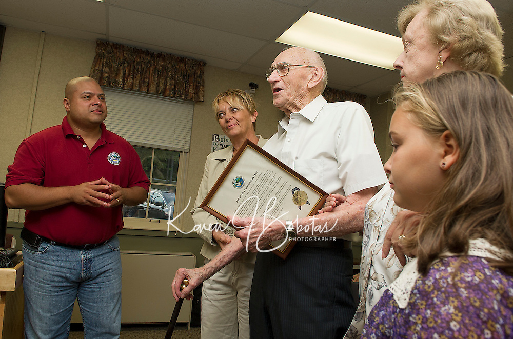 David Bickford accepts the Boston Post Cane from Gus Benevides prior to Wednesday evenings Selectmans meeting at the Gilford Town Hall.  Five generations surrounding Bickford are his granddaughter Alicia Gorrell, daughter Evelyn Firth, great great granddaughter Lydia Jordan (not in picture is great grand daughter Breinn Daigneault).   (Karen Bobotas/for the Laconia Daily Sun)