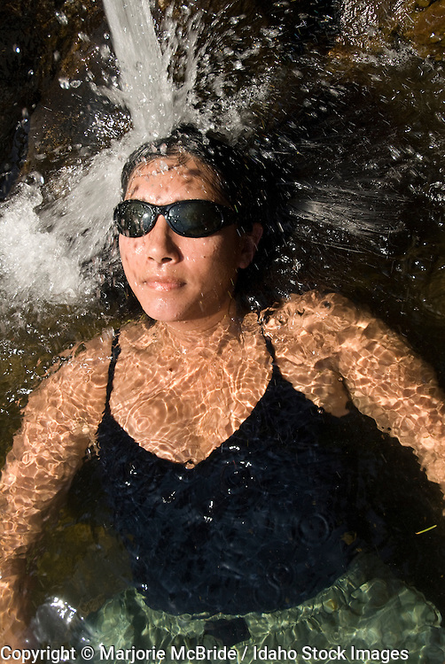 Woman enjoys shower in water from hot spring on the Main Salmon River in Idaho.    Model Release